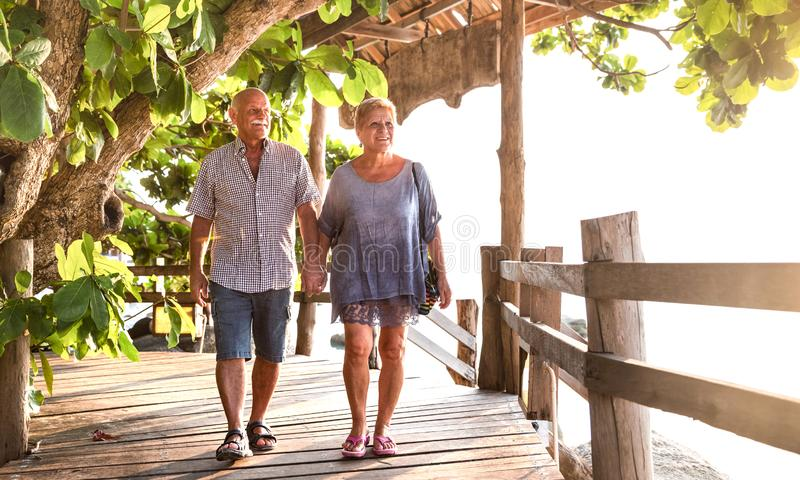 Happy senior couple walking holding hand at Koh Phangan beach promenade - Active elderly and travel lifestyle concept stock photos