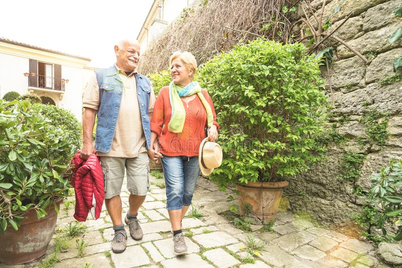 Happy senior couple walking holding hand in San Marino old town. Castle - Active elderly and travel lifestyle concept with retired mature people at Italy stock image