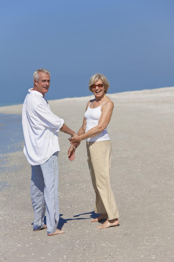 Download Happy Senior Couple Walking Holding Hands On Beach Stock Image - Image: 19443691