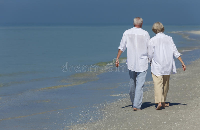 Happy Senior Couple Walking Holding Hands Tropical Beach. Rear view of happy senior men and women couple walking and holding hands on a deserted tropical beach