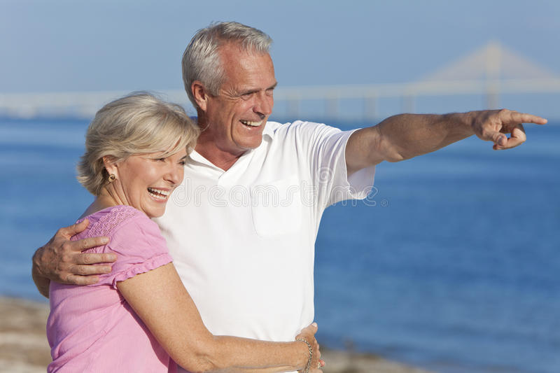 Download Happy Senior Couple Walking Pointing On Beach Stock Image - Image: 21826967