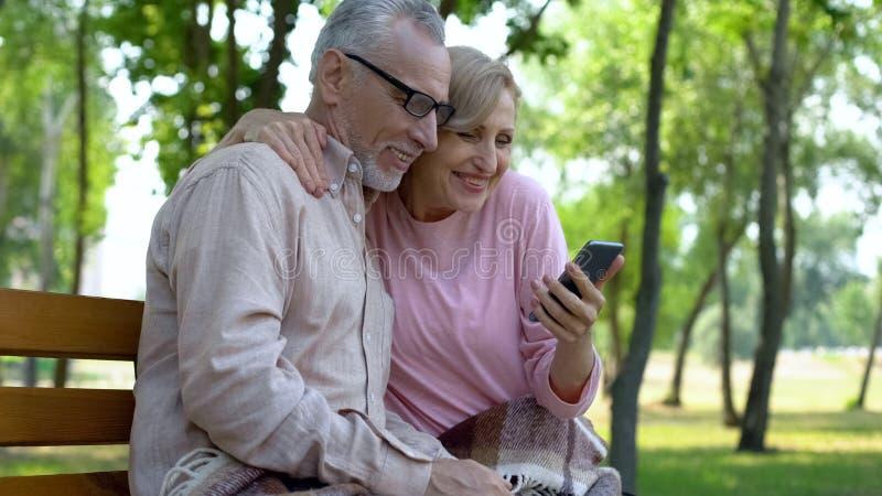Happy senior couple watching smartphone photos, retirement leisure in park stock photos