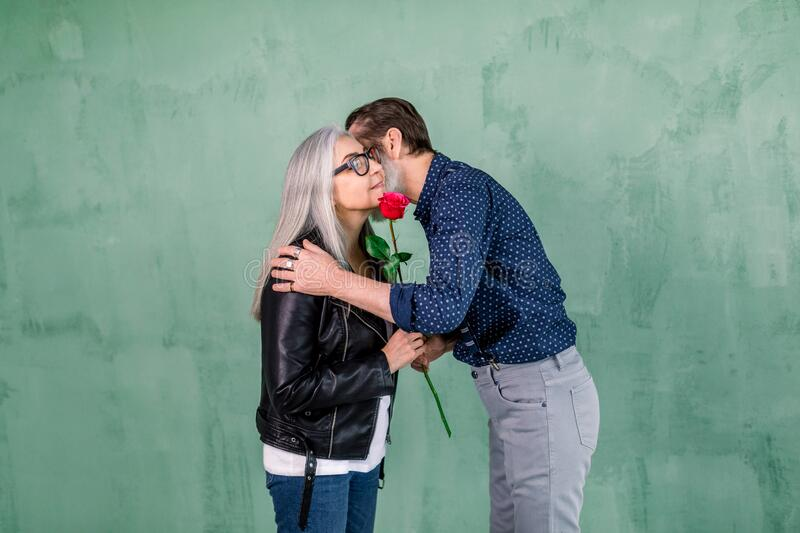 Happy senior family portrait. Handsome elderly bearded man giving beautiful red fresh rose to his charming smiling wife. And kissing her cheek, standing on royalty free stock photos