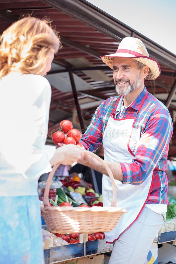 Happy senior farmer selling organic vegetables in a farmer`s marketplace stock images