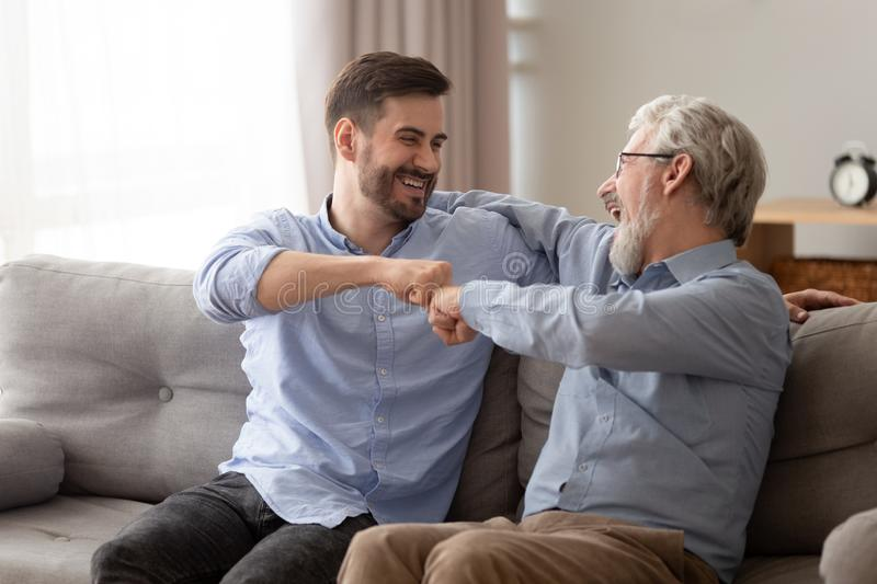 Happy senior father embracing young son giving fist bump. Happy family old senior father embracing young adult grown son giving fist bump sit on sofa having fun royalty free stock photography