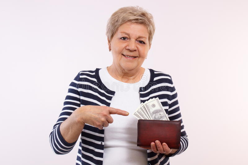 Happy senior female showing dollar currencies in wallet, concept of financial security in old age stock photo
