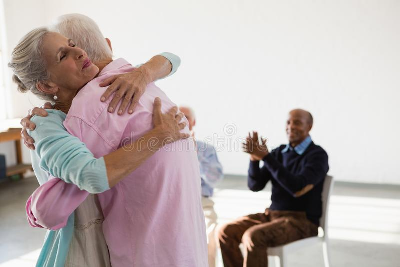 Happy senior friends applauding while looking at man and woman embracing stock photography