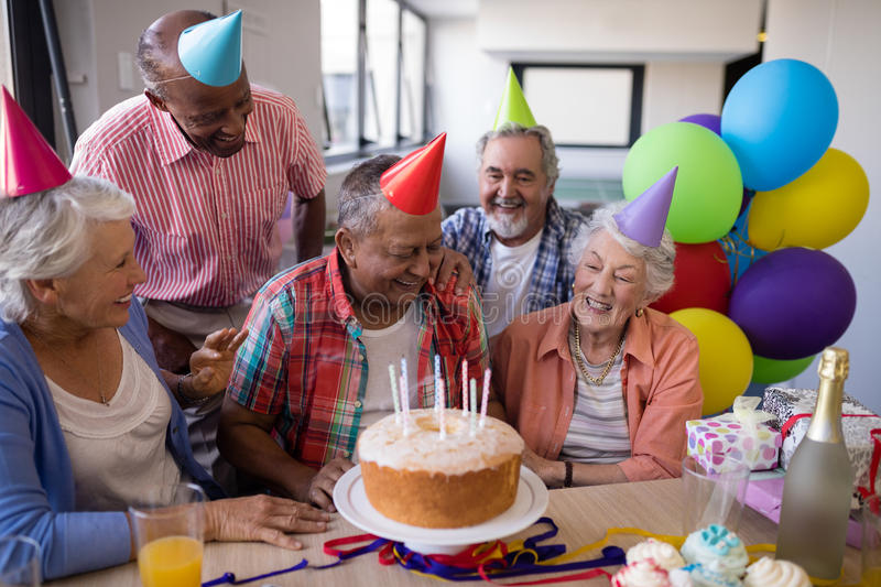 Happy senior friends by birthday cake at party. Happy senior friends by birthday cake celebrating at party in nursing home stock images