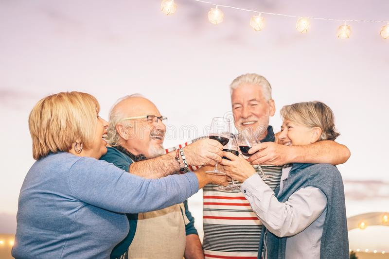 Happy senior friends cheering and toasting with red wine on terrace - Older people having fun at dinner party on patio at sunset royalty free stock image