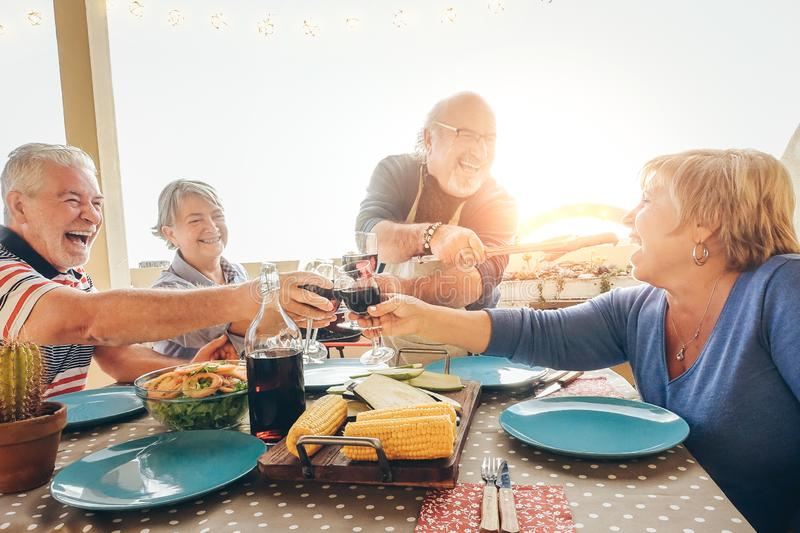 Happy senior friends having fun cheering with red wine at barbecue in terrace outdoor - Older people dining with grill meat royalty free stock photos