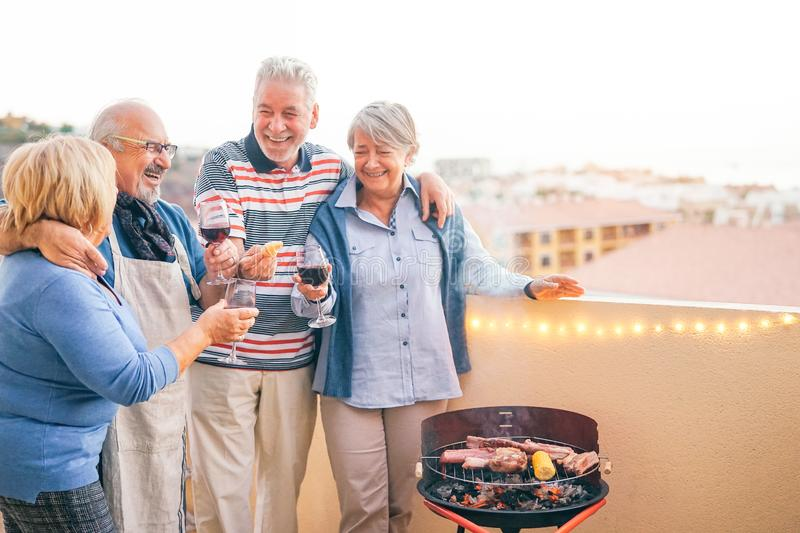 Happy senior friends having fun drinking red wine at barbecue dinner in terrace - Mature people dining and laughing together stock image