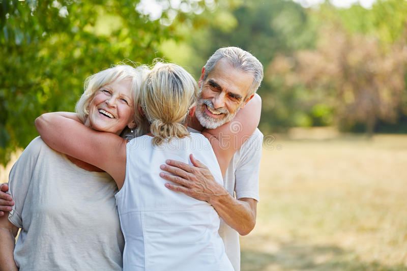 Happy senior friends hugging each other royalty free stock image