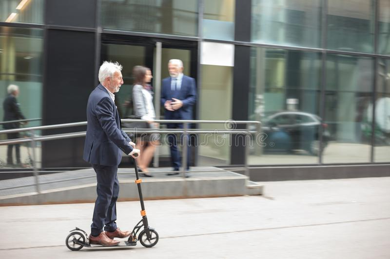 Happy senior businessman commuting to work on a kick scooter. Happy senior gray-haired businessman commuting to work on a kick scooter. Riding on a sidewalk in royalty free stock photography