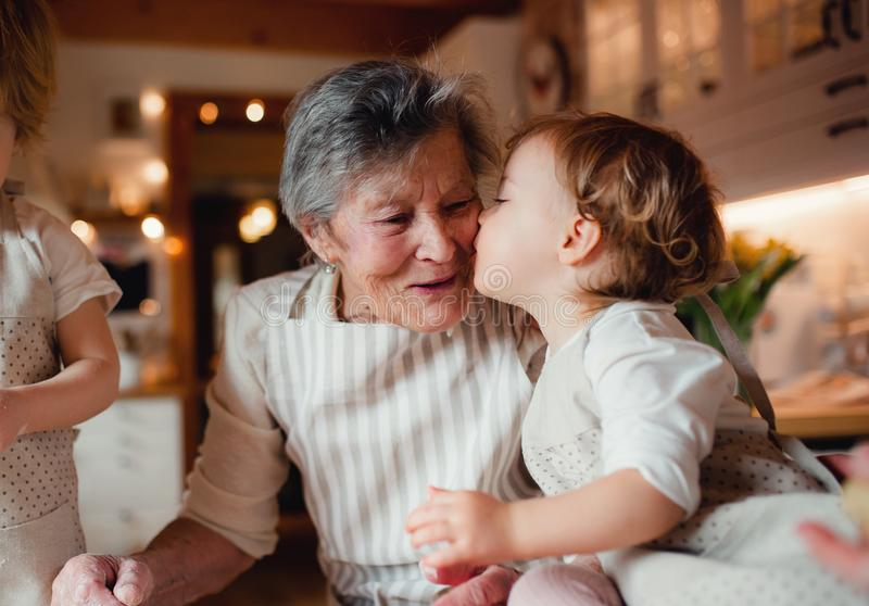 Senior grandmother with small toddler children making cakes at home. stock photos