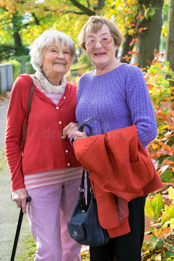 Happy Senior Ladies in Autumn Clothing. Three Quarter Shot of Two Happy Senior Ladies in Autumn Clothing Smiling at the Camera Against Plants and Trees stock photography