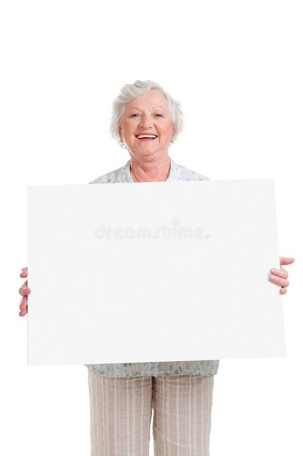 Happy senior lady with sign stock photo