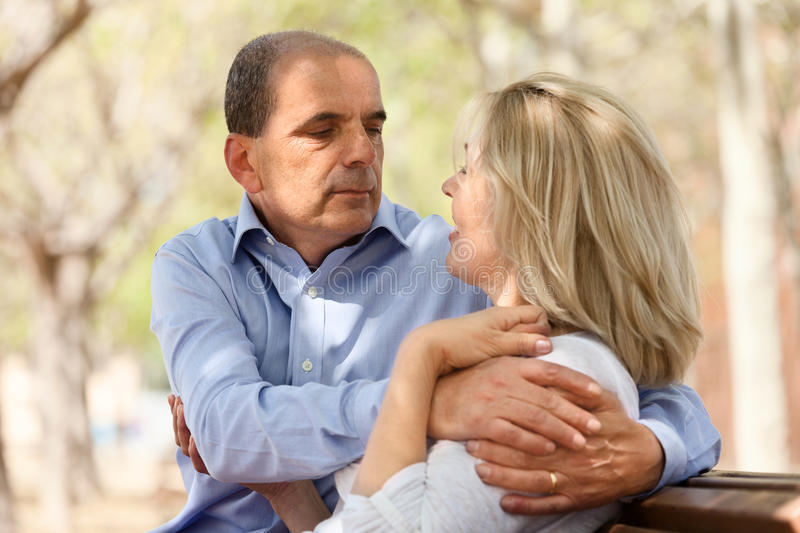 Happy senior lovers hugging each other. In summer park royalty free stock photo