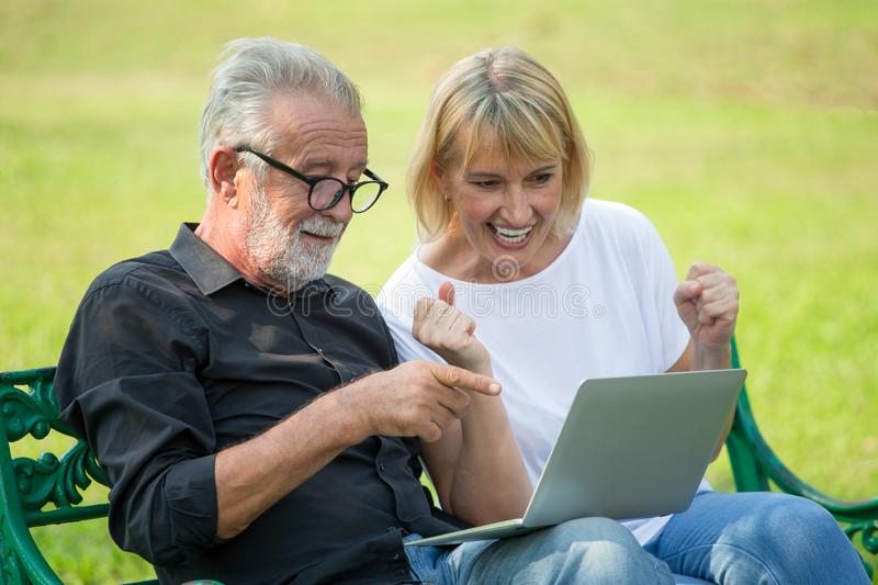 Happy senior loving couple relaxing with laptop computer at park excited together in morning time. old people sitting on a bench stock photography