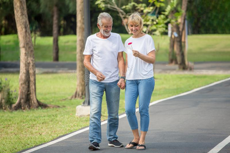 Happy senior loving couple relaxing at park walking with flower together in morning time. old people holding hand and enjoying royalty free stock images