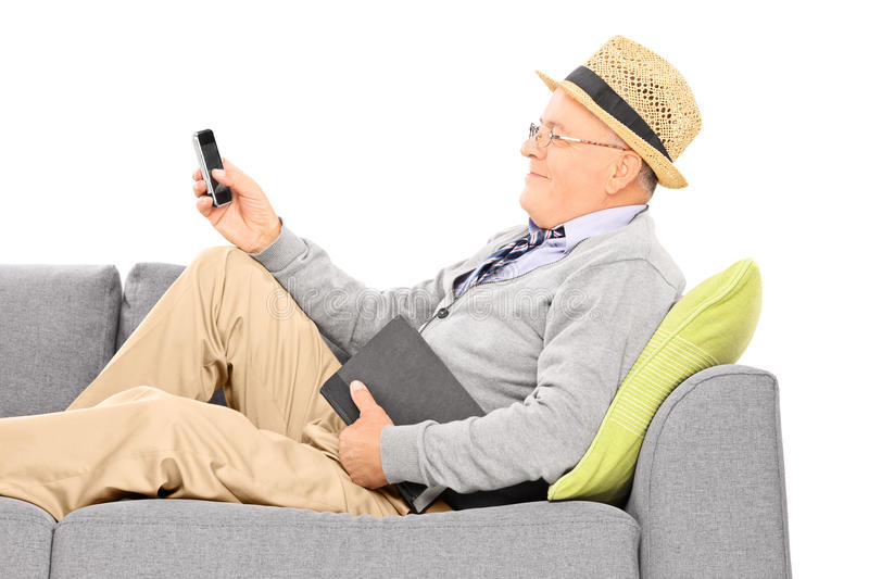 Happy senior lying on couch and typing an sms. Isolated on white background royalty free stock photography