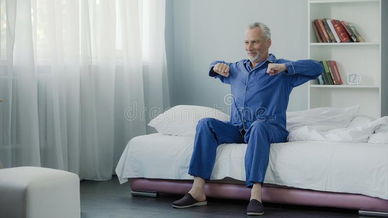 Happy senior male doing morning gymnastics in his bed, good mood, optimistic royalty free stock photos