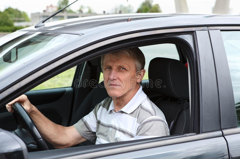 Happy senior male sitting in car on driver seat. And smiling royalty free stock images
