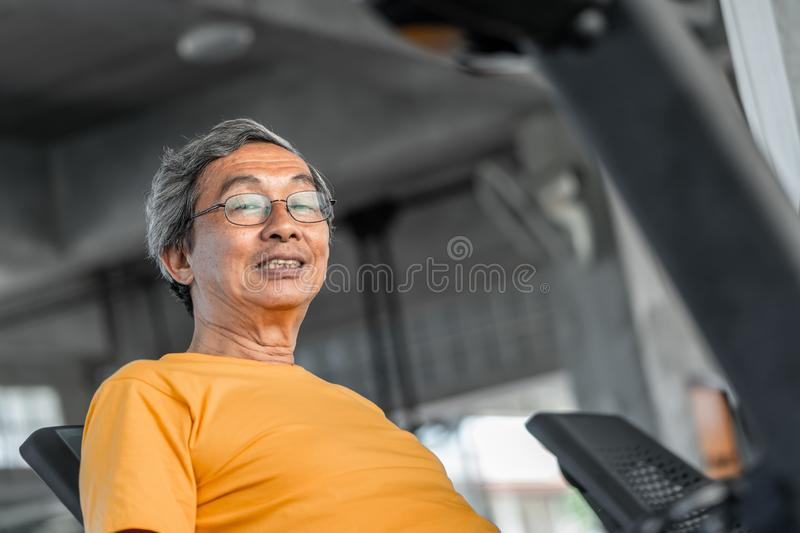 Happy Senior is working out on fitness machine for elder healthy concept royalty free stock images