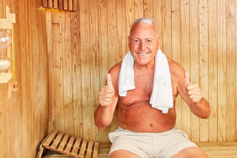 Manager in the sauna keeps thumbs up stock images