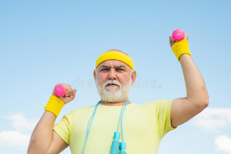 Happy senior man with dumbbell looking at camera. Health club or rehabilitation center for elderly aged pensioner royalty free stock images