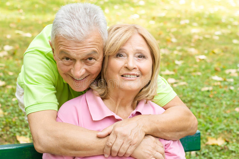Happy senior man embracing her wife stock photos