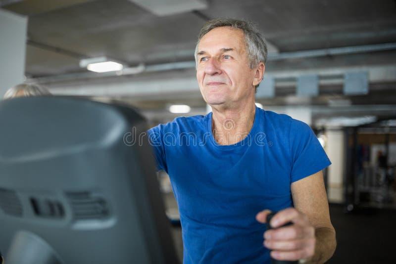 Happy senior man exercising on stair stepper at gym. Portrait of happy senior man exercising on stair stepper at gym royalty free stock photo