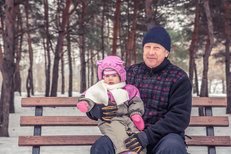 Happy senior man with his granddaughter sitting on bench during walking in winter park in snowy weather during winter holidays stock photography