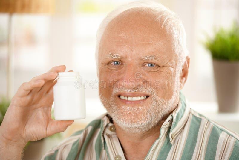 Happy senior man holding medication. Closeup portrait of happy senior man holding medication phial, blank space stock photography