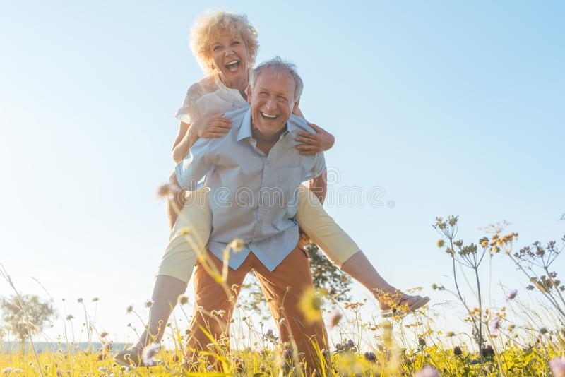 Happy senior man laughing while carrying his partner on his back. Low-angle view portrait of a happy senior men laughing while carrying his partner on his back royalty free stock photo