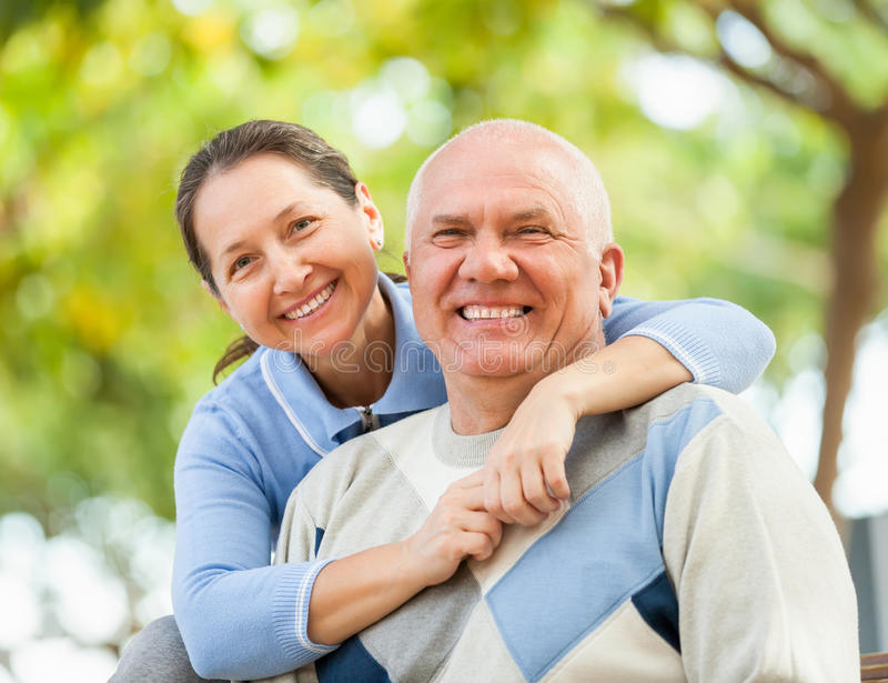 Happy senior man and mature woman against the park stock photo