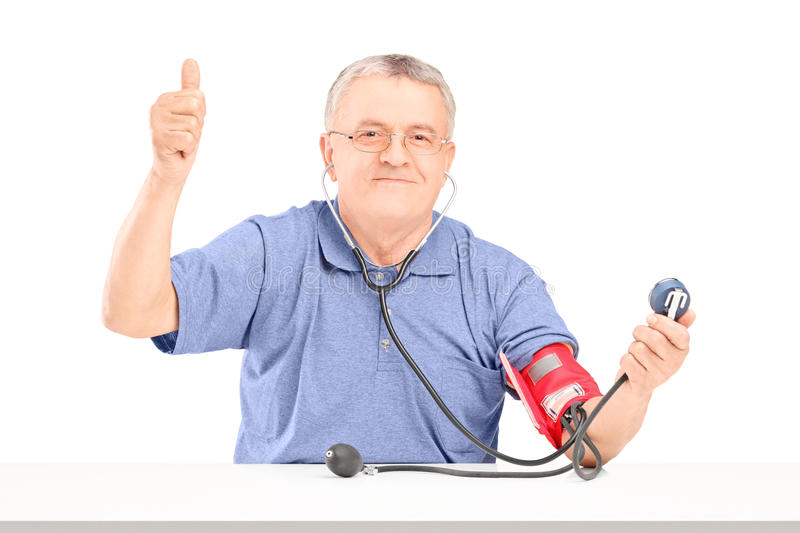 Happy senior man measuring blood pressure and giving a thumb up. On white background royalty free stock photography