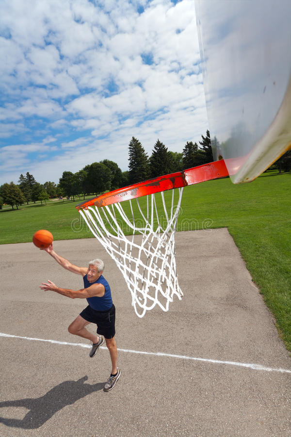Happy senior man playing basketball. Active senior man shoots hoops on a basketball court outdoors. Background is grass, trees, and blue sky with fluffy clouds royalty free stock photography