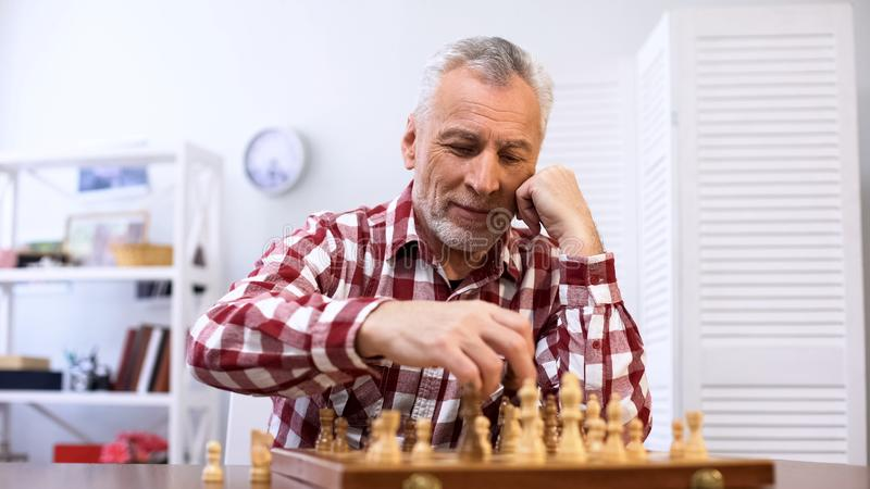Happy senior man playing chess alone, training for chess competition, checkmate royalty free stock image