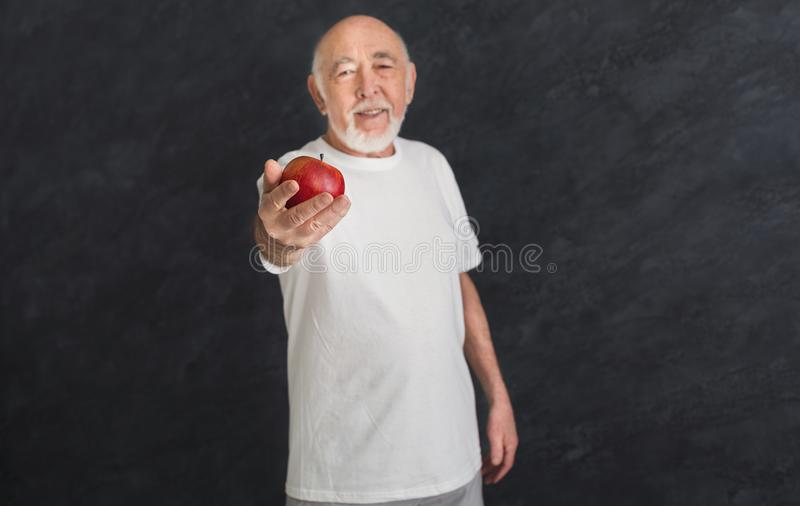 Happy senior man proposing red apple to you. Happy smiling senior man proposing red apple to you, agitating for healthy eating, black background. Active stock images