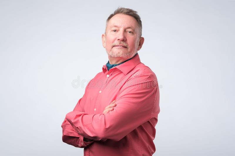 Happy senior man in red shirt looking with confidence stock images