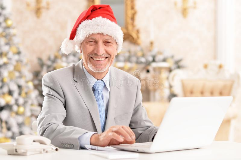 Portrait of senior man working with laptop. Happy senior man in Santa hat working with laptop at home stock photography
