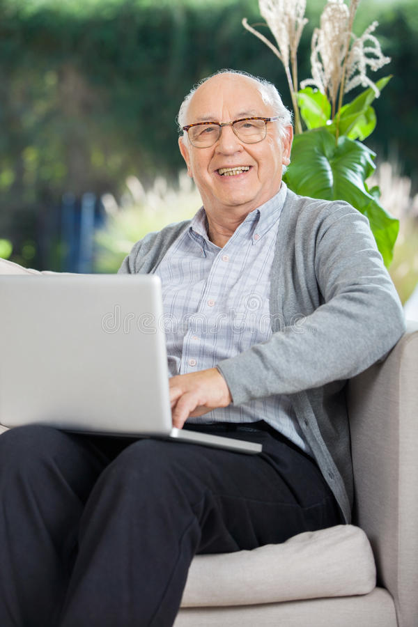Happy Senior Man Sitting With Laptop On Couch royalty free stock photos