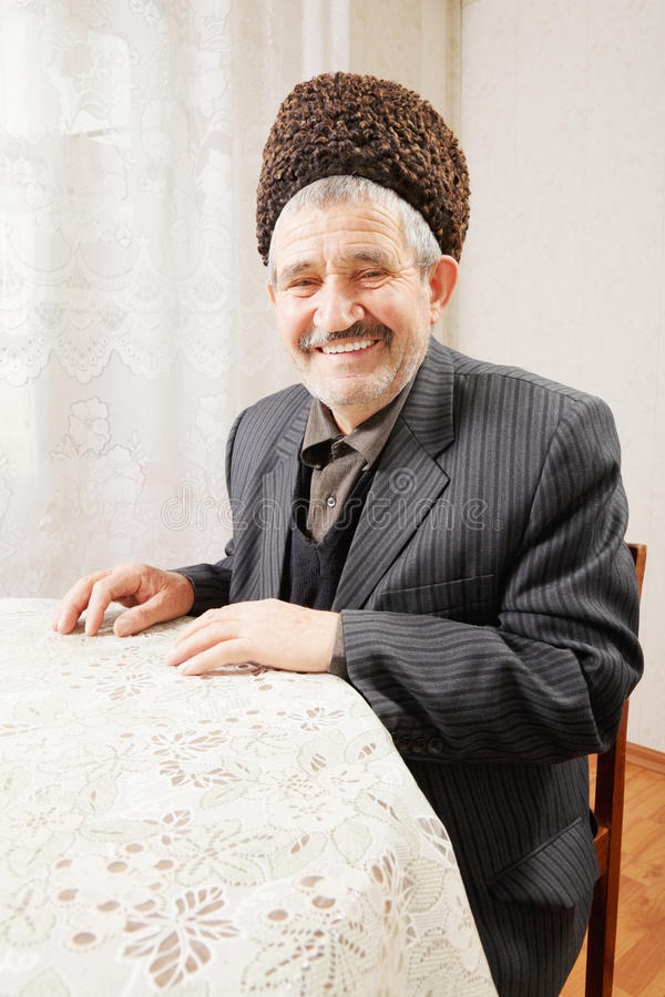Happy senior man sitting at table stock image