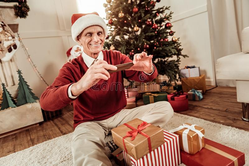 Happy senior man smiling and making photo. Remember this moment. Happy senior occupied man In a red hat sitting on the floor near presents smiling and making stock photography