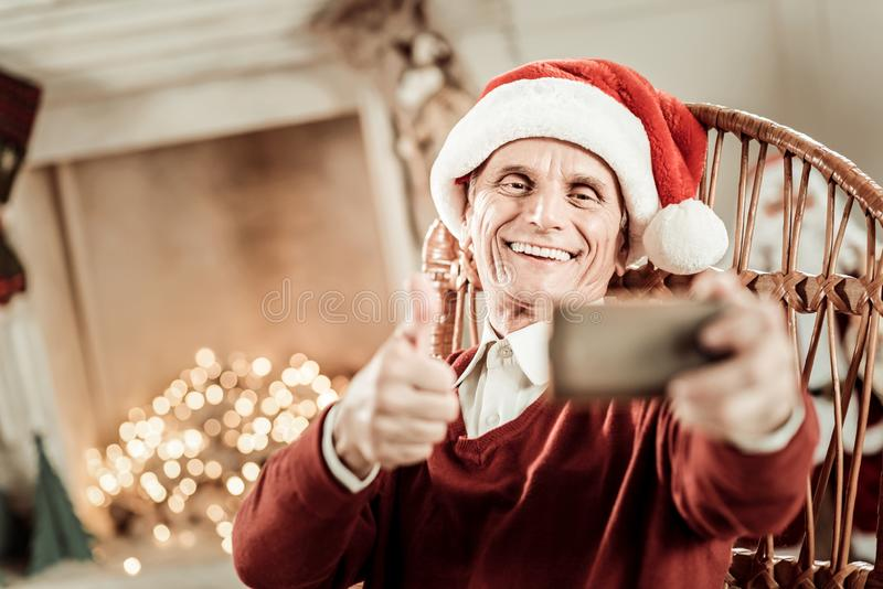 Happy senior man smiling and making selfie. Holiday and fun. Happy senior funny man in a red hat sitting on the chair smiling and making selfie stock image