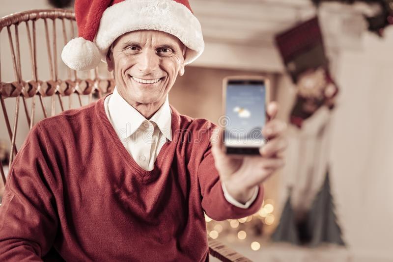Happy senior man smiling and showing his cellphone. Look at this. Happy senior joyful man in a red hat sitting on the chair smiling and showing his cellphone royalty free stock images