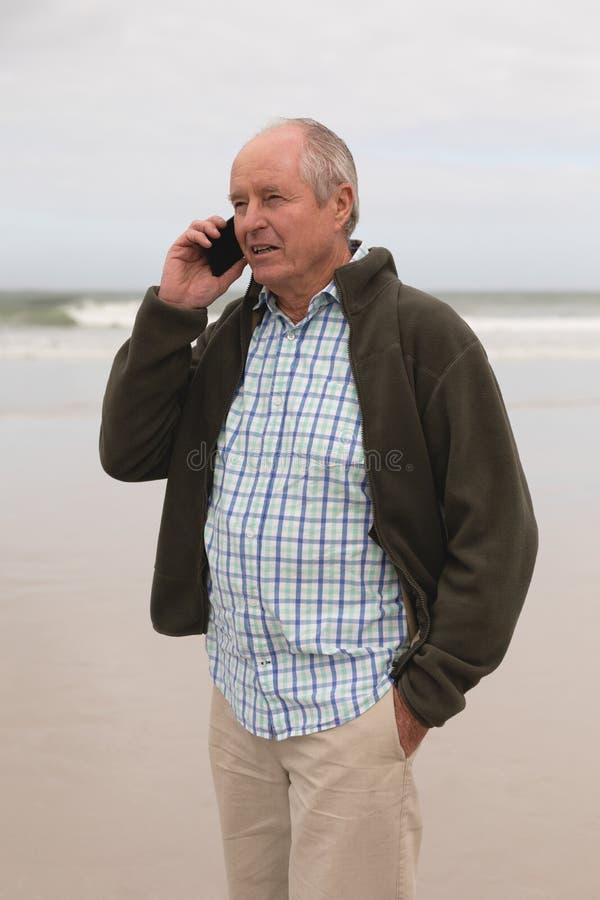 Happy senior man talking on mobile phone at beach stock image