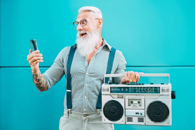 Happy senior man using mobile phone while holding vintage boombox outdoor - Fashion hipster male having fun listening music royalty free stock photos