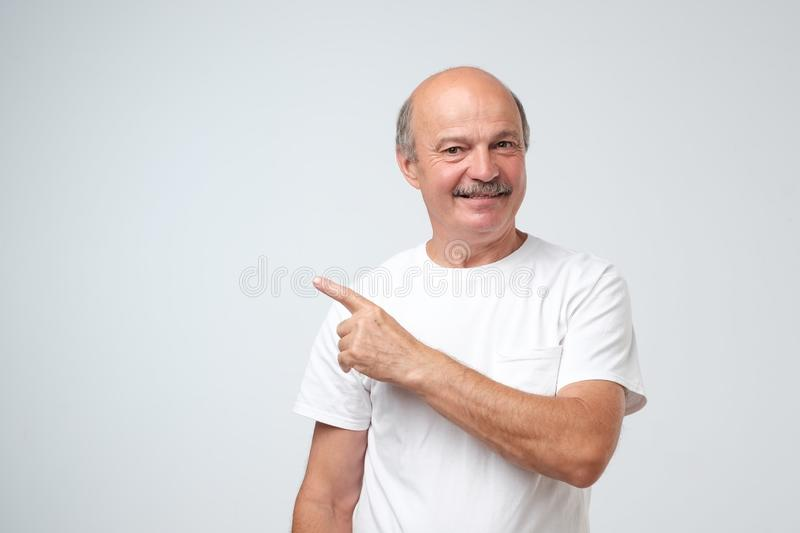 Happy senior man in white t-shirt looking at camera, smiling and pointing aside with hand. royalty free stock image