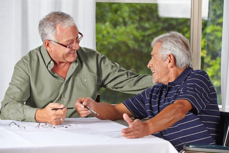 Happy senior men solving crossword royalty free stock image